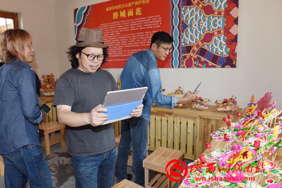 当日,河南黄河科技学院艺术设计学院副院长、副教授杨庆平被精美绝伦的澄城面花所吸引,用电子设备拍照留念。记者 杨青山 摄