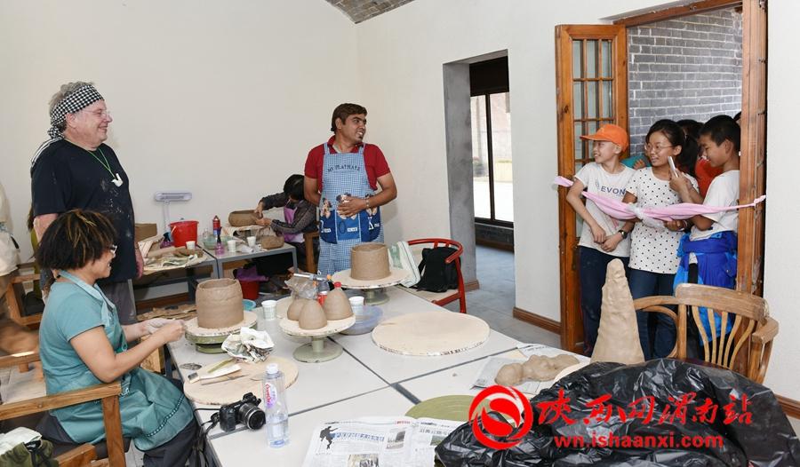 陶艺专家集中精力,互相切磋,他们手法娴熟、技艺高超,彰显出陶艺创作的无穷魅力,吸引游客小朋友前来参观。记者 杨青山 摄
